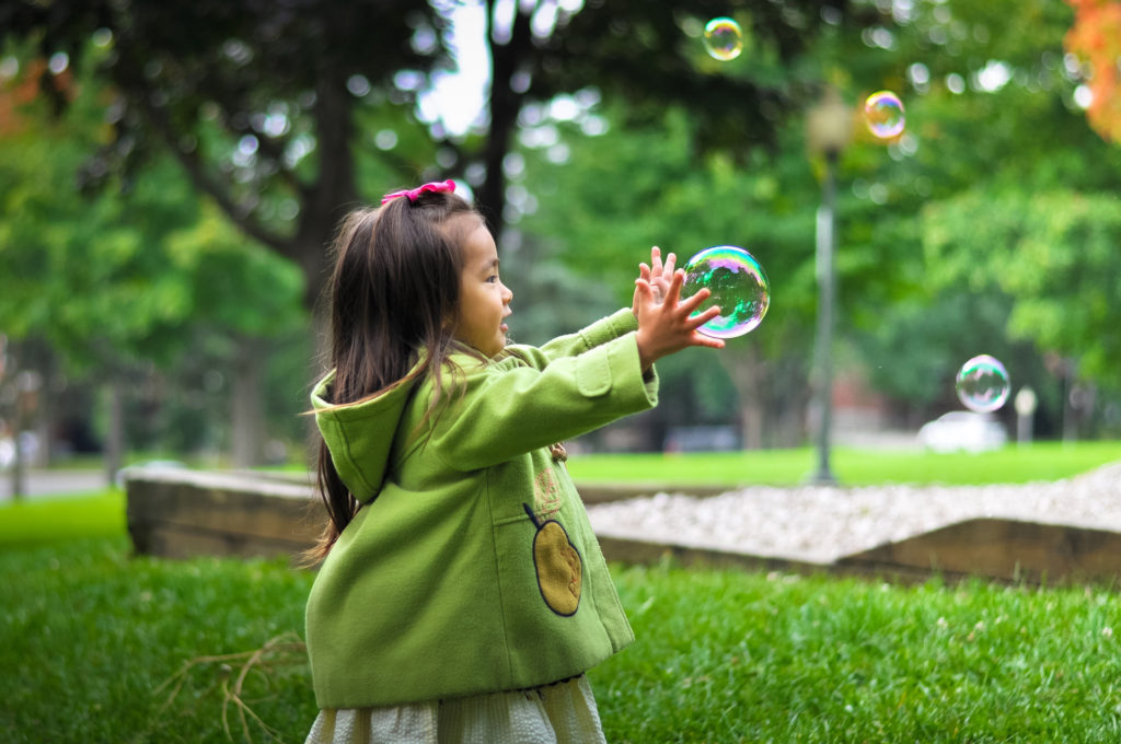 Girl with bubbles in park