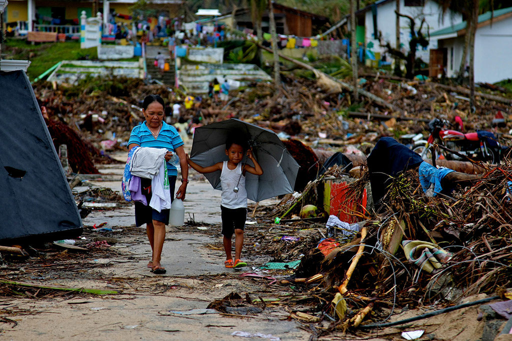 mother and son walking through debris