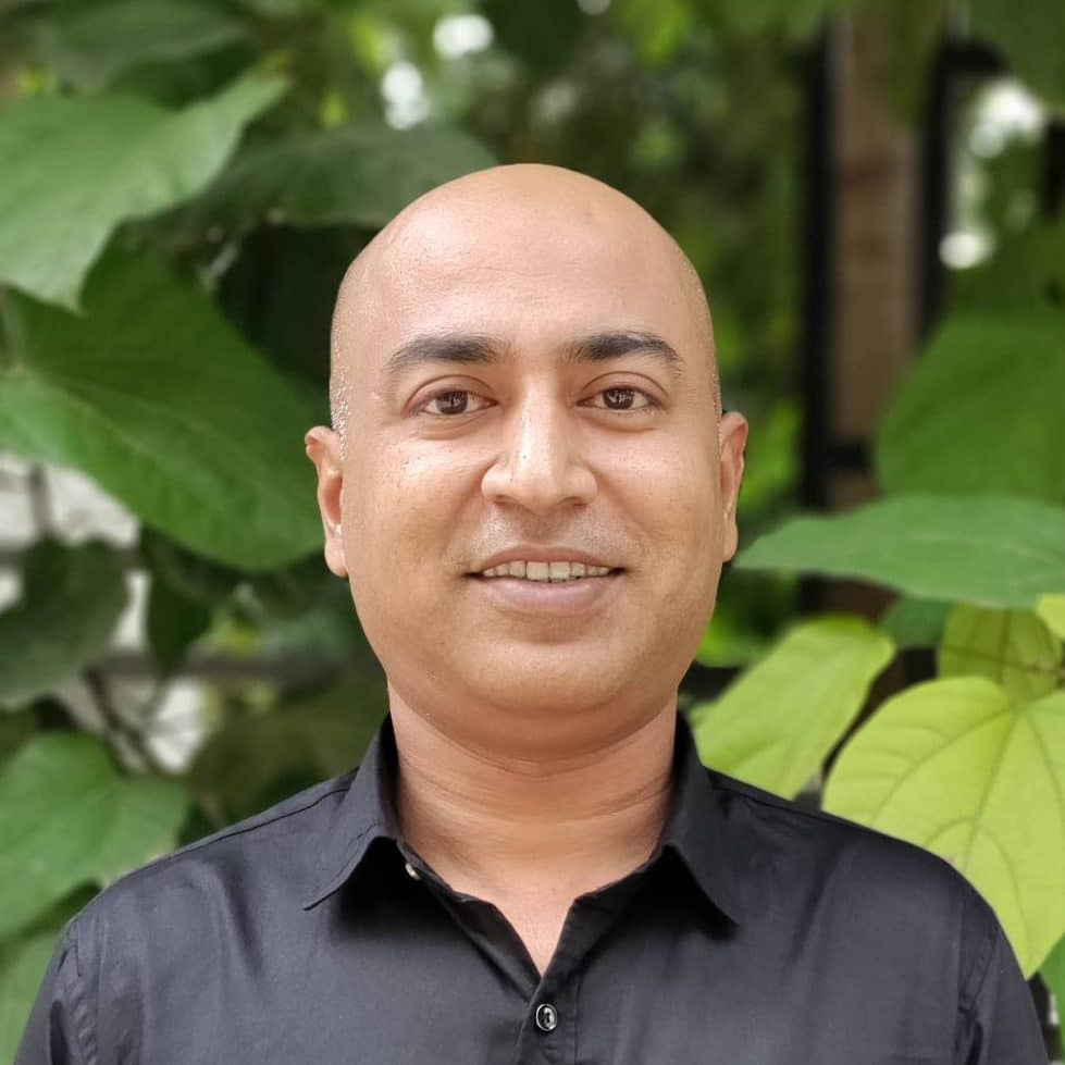 A headshot of Prashant Pandit, smiling in front of foliage in a black dress shirt.